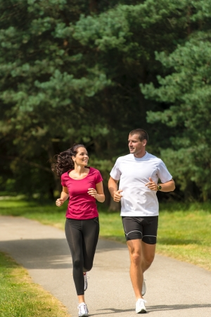 running out of time: Smiling young couple running in park Stock Photo