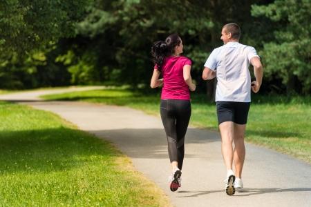 personas trotando: Vista trasera de raza cauc�sica mujeres y hombres corredores al aire libre