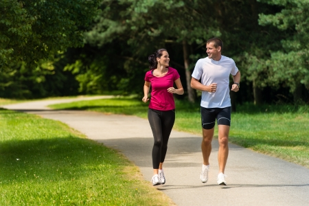 jogging in park: Cheerful Caucasian couple friends running in park