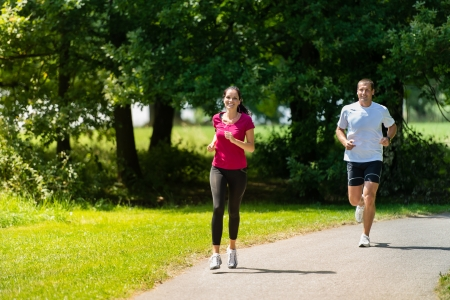 Caucasian boyfriend and girlfriend running a race in sunny park Stock Photo - 22213230