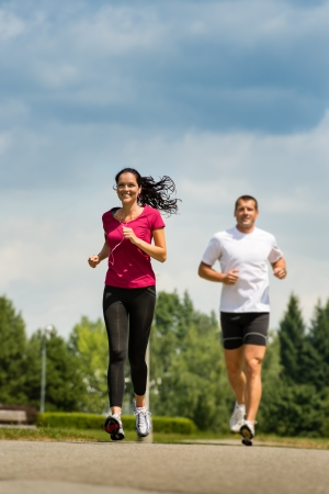 Playful couple friends running a race in a park Stock Photo - 22213242