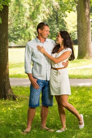 Cuddling boyfriend and girlfriend standing in park Stock Photo - 22213255