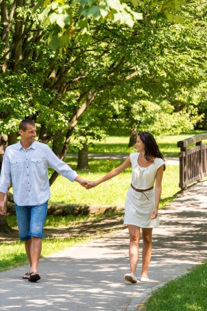 Cheerful couple in love holding hands outdoors walking in park photo