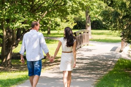 pareja de esposos: Vista posterior de la pareja caminando en el parque cauc�sico