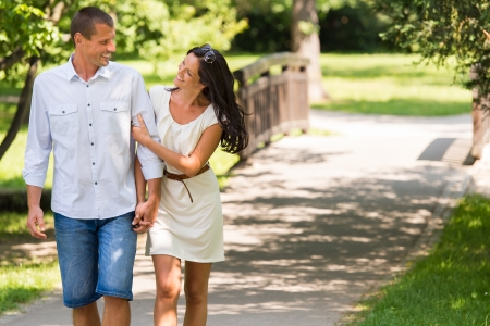 Cheerful Caucasian couple walking outdoors hand in hand