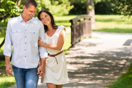 Smiling couple walking in a park hand in hand photo