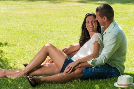 Hugging couple laughing and sitting in grass outdoors Stock Photo - 22213583