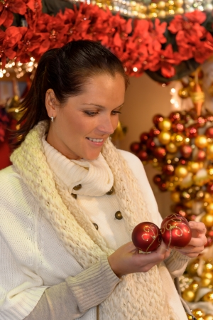 Smiling woman customer holding Christmas baubles at shop photo