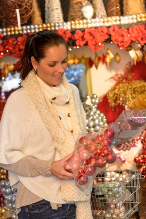 Happy woman buying Christmas decoration in plastic boxes photo