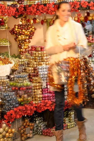 Smiling blurry woman buying shiny Christmas ornaments in shop photo