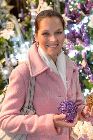 Smiling woman with shiny Christmas balls at wintertime photo