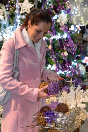 Happy woman putting sparkling Christmas decorations to shopping basket photo