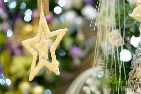 Sparkling gold star ornament hanging from Christmas tree Stock Photo - 22175227