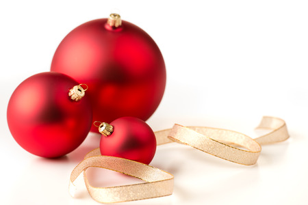 Red christmas baubles and gold ribbons on a white background Stock Photo - 22396460