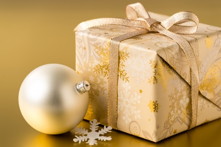 Christmas present and silver bauble on gold background Stock Photo - 22396463