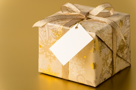 Christmas present with ribbon and blank tag on gold background copyspace Stock Photo - 22396465
