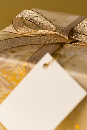 Christmas gift with blank tag focus on gold ribbon Stock Photo - 22396466