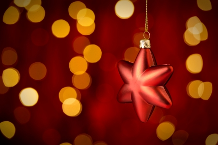 Hanging Christmas Ornament star with sparkling lights in background photo