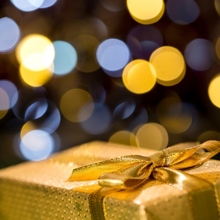 wrapped present: Christmas gift with sparkling lights background wrapped in gold paper