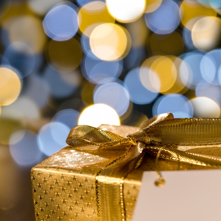 wrapped present: Golden Christmas gift with label sparkling lights on background