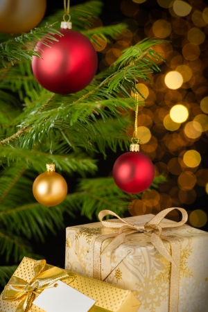 Christmas decoration tree, baubles and gifts on shining lights background photo