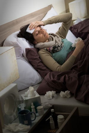nose drops: Sick woman with flu lying in bed suffering from headache