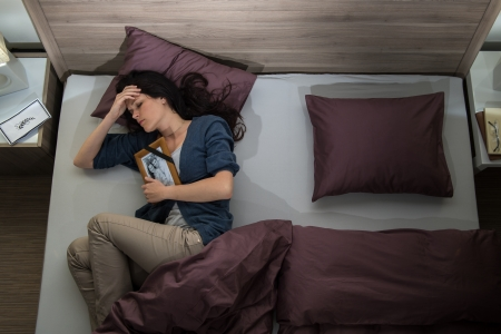 lonely person: Lonely woman lying in bed missing her dead husband