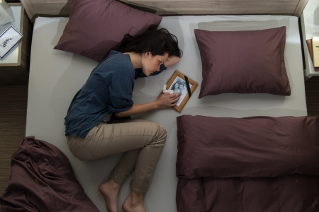 Young mourning woman lying in bed alone Stock Photo