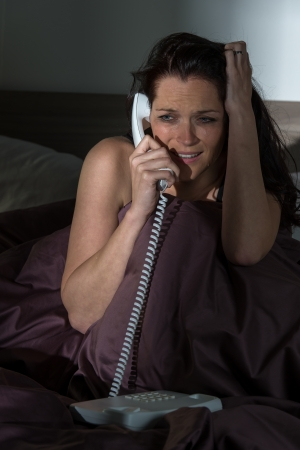 freaked: Scared crying Caucasian woman phoning in bed Stock Photo