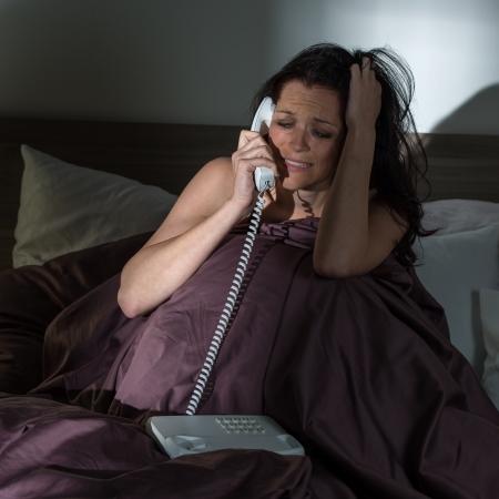 Pleurer jeune femme appelant téléphone dans son lit Banque d'images