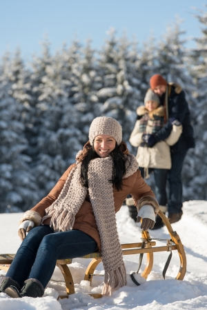 Young woman sitting winter wooden sledge friends in sunny background photo