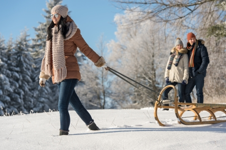 Young woman pulling winter sledge couple walking through snow countryside photo