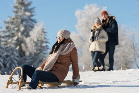 Friends enjoy sunny winter day on wooden sledge photo