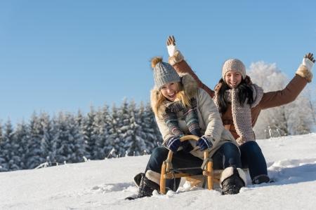Deux copines luge descente sous le soleil de la neige en hiver luge en bois