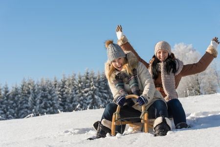 Two girlfriends sledge downhill in sunny wintertime snow wooden sledge Stock Photo