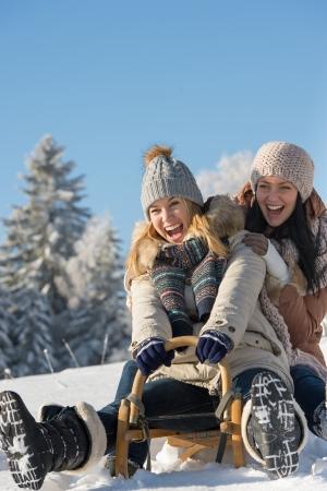 Adolescents rire luge descente en hiver profiter de la neige Banque d'images