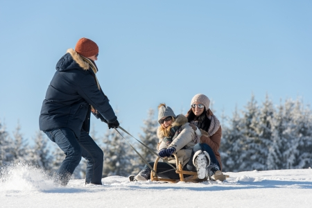 Young man pulling girls on winter sledge snow countryside photo