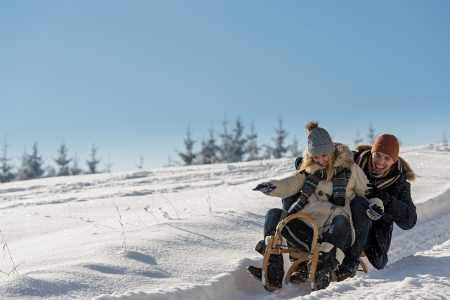 Young playful couple having fun in the snow sledging downhill photo