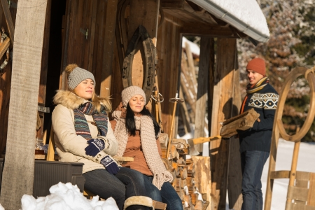 sunny cold days: Young people by wooden winter cottage enjoying sunshine outdoor