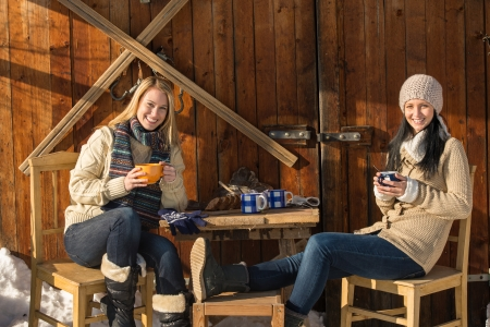 Two young women enjoy tea winter cottage wooden sunny outdoor photo