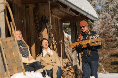 chalets: Young man carry wooden log winter cottage snow girlfriends sunbathing