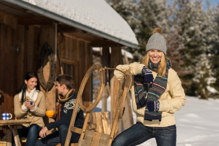 Young woman with friends spending holiday in winter snow cottage photo
