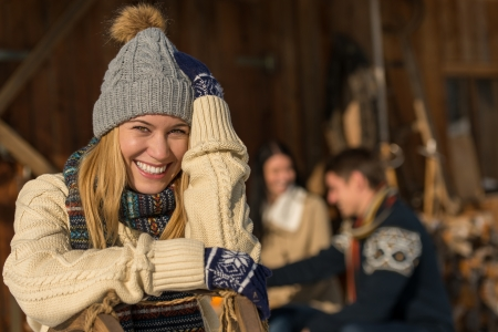 Young smiling woman in winter clothes cottage enjoy holiday friends photo