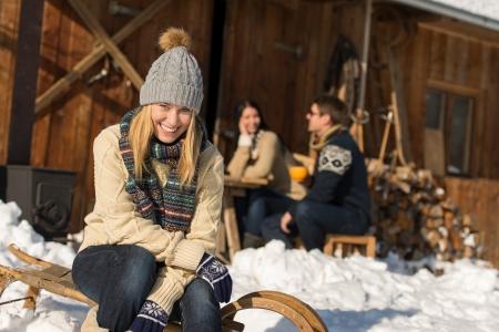 Jeune femme avec des amis profiter pause week-end neige chalet d'hiver