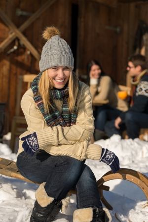 holiday spending: Young woman sitting winter snow sledge cottage spending holiday friends