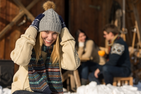 Young woman in winter hat spend time in snow cottage photo