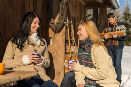 chalets: Friends spend holiday winter snow cottage enjoy tea outside