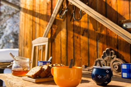Breakfast on wooden table outside winter snow cottage photo