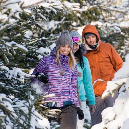 Three friends walking through snow winter forest photo