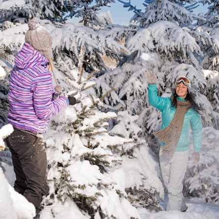 snow break: Two girlfriends throw snow balls winter forest enjoy holiday break Stock Photo
